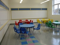 Small, multicolored tables and chairs with whiteboards on walls